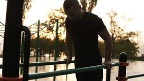 Il ritratto di giovane maschio muscolare caucasico che fa la tirata aumenta gli esercizi sulla barra orizzontale all'aperto Addes stock footage