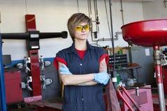Il ritratto di giovane meccanico femminile che indossa l'ingranaggio protettivo con le armi ha attraversato in officina Immagini Stock Libere da Diritti