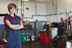 Il ritratto di giovane meccanico femminile sicuro con le armi ha attraversato in garage Immagine Stock