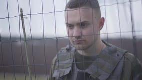 Il ritratto di giovane militare coraggioso ha messo a fuoco stare dietro la rete metallica e la custodia dell'area militare stock footage