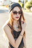 Il ritratto di giovane ragazza alla moda dei pantaloni a vita bassa si è vestito in cappuccio ed occhiali da sole scuri immagine stock libera da diritti