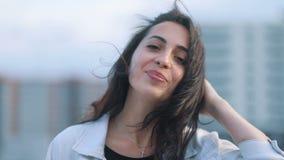 Il ritratto di giovane ragazza castana caucasica di stupore attraente in jeans blu-chiaro ricopre di capelli d'ondeggiamento che  stock footage