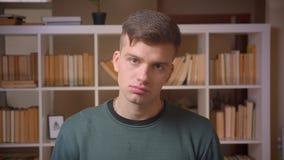 Il ritratto di giovane studente maschio che è premuroso ascolta ed annuisce col capo nell'accordo alla biblioteca archivi video