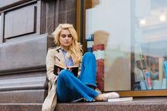 Il ritratto di giovane studentessa affascinante con il libro di lettura di lusso dei capelli biondi prima dell'inizio parla in un Fotografie Stock