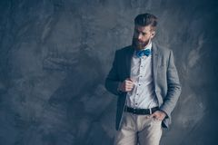 Il ritratto di giovane tipo barbuto in un vestito sta su un backgro grigio fotografia stock