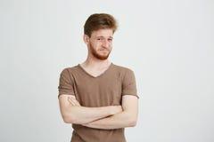 Il ritratto di giovane uomo bello con la barba che esamina la macchina fotografica con disprezzo ha attraversato le armi sopra fo Immagini Stock Libere da Diritti