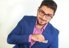 Il ritratto di giovane uomo d'affari sorridente con la barba elimina i soldi dalla sua tasca in vestito su fondo bianco immagine stock