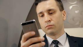 Il ritratto di giovane uomo d'affari sta utilizzando lo smartphone che si siede in aeroplano durante il volo archivi video