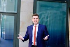 Il ritratto di giovane uomo d'affari In un vestito dà la sua mano per una stretta di mano, dell'interno Fotografie Stock Libere da Diritti