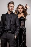 Il ritratto di giovani coppie attraenti che posano allo studio si è vestito in vestiti alla moda neri. Immagine Stock