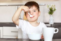 Il ritratto di Horiontal del bambino maschio attraente mangia il porridge delizioso con latte, condito in maglietta bianca casual Fotografie Stock