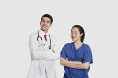 Il ritratto di medico maschio e dell'infermiere femminile che stanno con le mani ha ripiegato il fondo grigio fotografia stock libera da diritti