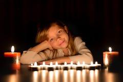 Il ritratto di piccola ragazza caucasica bionda sta mettendo nello scuro intorno alle candele Guarda in avanti Fotografia Stock
