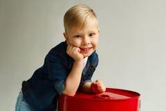 Il ritratto di piccolo bel ragazzo divertente in denim copre sopra bianco Fotografia Stock