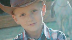 Il ritratto di piccolo cowboy alla moda con le mani attraversate esamina la macchina fotografica lentamente stock footage