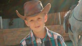 Il ritratto di piccolo cowboy alla moda sta vicino al cavallo di razza su luce solare lentamente archivi video
