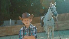 Il ritratto di piccolo cowboy alla moda sta vicino al cavallo di razza su luce solare lentamente stock footage