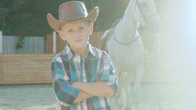 Il ritratto di piccolo cowboy con le mani attraversate si avvicina al cavallo su luce solare lentamente archivi video