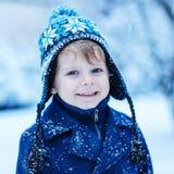 Il ritratto di piccolo ragazzo del bambino nell'inverno copre con Sn di caduta Fotografie Stock