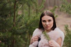 Il ritratto di ragazza molto bella in una foresta si è vestito in pelliccia Fotografia Stock