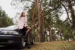 Il ritratto di ragazza molto bella in una foresta si è vestito in pelliccia in un'automobile Fotografia Stock