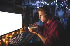 Il ritratto di un adolescente che si siede a casa in una stanza accogliente vicino ad un computer e mangia una minestra di pasta immagini stock