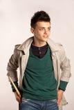 Il ritratto di un batterista con il bastone del tamburo che porta un cappotto e greeen la camicia in studio Fotografia Stock
