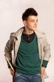 Il ritratto di un batterista con il bastone del tamburo che porta un cappotto e greeen la camicia in studio Immagine Stock