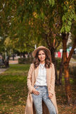 Il ritratto di un cappello d'uso della ragazza ed il cappotto in autunno parcheggiano Immagine Stock