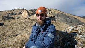 Il ritratto di un fotografo barbuto del viaggiatore in occhiali da sole ed in un cappuccio si siede su una roccia con la macchina archivi video