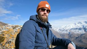 Il ritratto di un fotografo barbuto del viaggiatore in occhiali da sole ed in un cappuccio si siede su una roccia con la macchina video d archivio