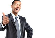 Il ritratto di un gesturing afroamericano sorridente dell'uomo di affari pollici aumenta il segno Fotografie Stock