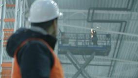 Il ritratto di un ingegnere in un casco che accende il saldatore e poi esamina la macchina fotografica nell'industriale moderno stock footage