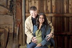 Il ritratto di un mezzo ged l'uomo e la sua moglie incinta nel loro granaio Fotografie Stock Libere da Diritti