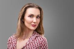Il ritratto di un mezzo sorridente ha invecchiato la donna caucasica su fondo grigio immagini stock libere da diritti