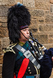Il ritratto di un militare ha vestito il suonatore di cornamusa che gioca la cornamusa Immagine Stock Libera da Diritti