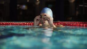 Il ritratto di un nuotatore maschio mette gli occhiali di protezione sopra di nuoto video d archivio