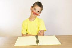 Il ritratto di un ragazzo sporgente le labbra, scolaro uno scherzo e non vuole a fotografia stock libera da diritti