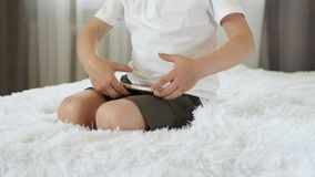 Il ritratto di un ragazzo, sta sedendo su un letto e sta giocando con uno smartphone Sviluppo moderno, istruzione della scuola ma video d archivio