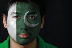 Il ritratto di un uomo con la bandiera del Pakistan ha dipinto sul suo fronte su fondo nero fotografia stock