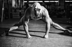 Il ritratto di un uomo di forma fisica che fa l'allungamento si esercita alla palestra Fotografia Stock