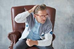 Il ritratto di un uomo intelligente alla moda con i vetri fissa nella macchina fotografica Fotografia Stock