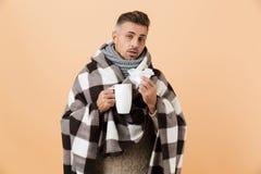 Il ritratto di un uomo malato triste si è avvolto in una coperta fotografie stock