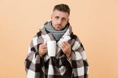 Il ritratto di un uomo malato triste si è avvolto in una coperta fotografia stock