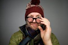 Il ritratto di un uomo maturo divertente nell'inverno caldo copre l'esame della macchina fotografica attraverso i vetri sopra fon immagine stock