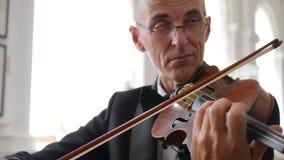 Il ritratto di un violinista, uomo anziano in vetri gioca sulle fiddle di legno archivi video