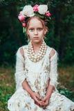 Il ritratto di una bambina con la corona della peonia fiorisce Fotografia Stock Libera da Diritti