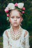 Il ritratto di una bambina con la corona della peonia fiorisce Fotografia Stock