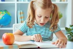 Il ritratto di una bambina sveglia ha letto il libro alla tavola in aula immagini stock