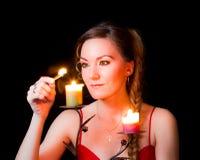 Il ritratto di una candela della ragazza illumina una corrispondenza Fotografia Stock